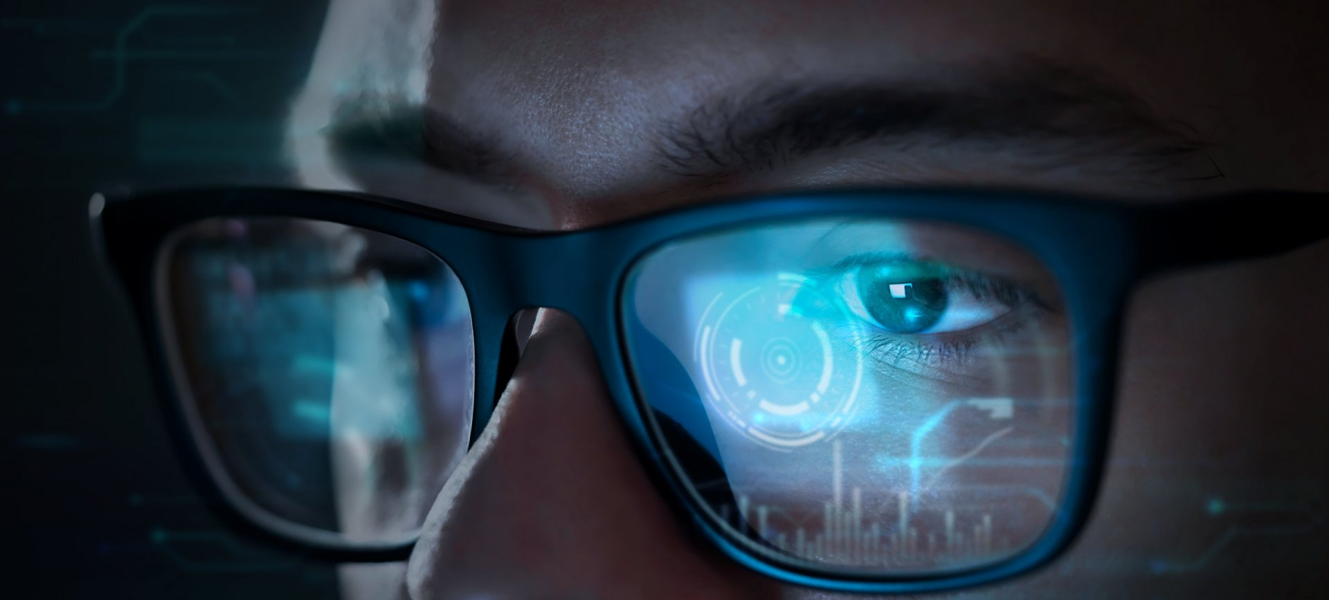 A SOC analyst's glasses reflecting data displayed on a a computer screen